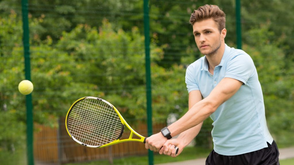 Ready to beat the ball. Confident young man is standing and posing. He is holding a tennis racket and looking forward with aspiration